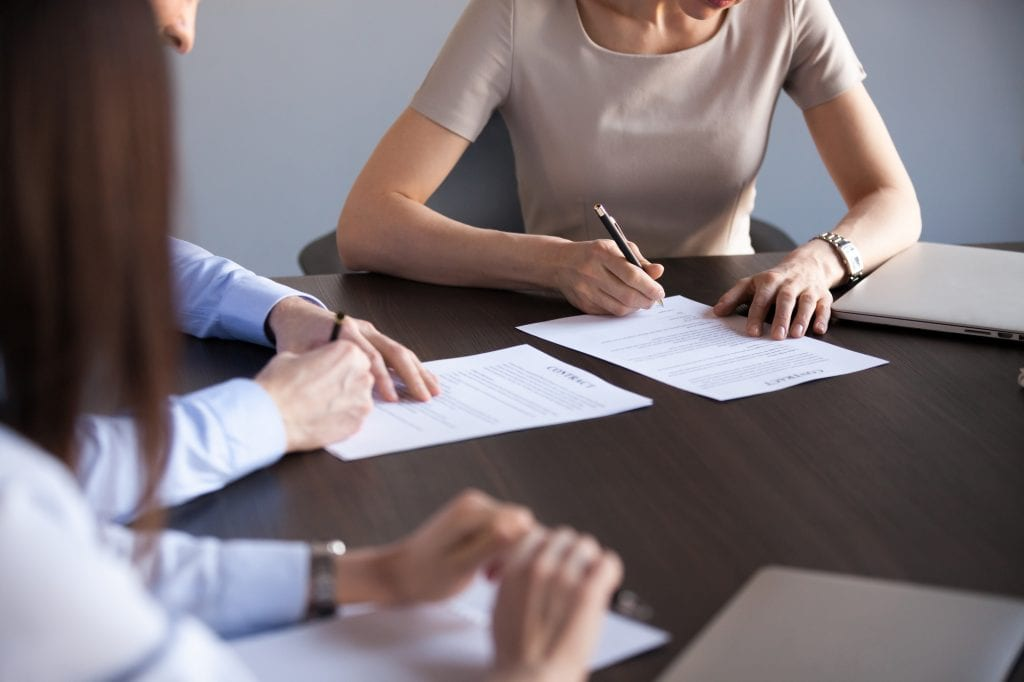 Couple reviews and signs documents during a divorce mediation session.
