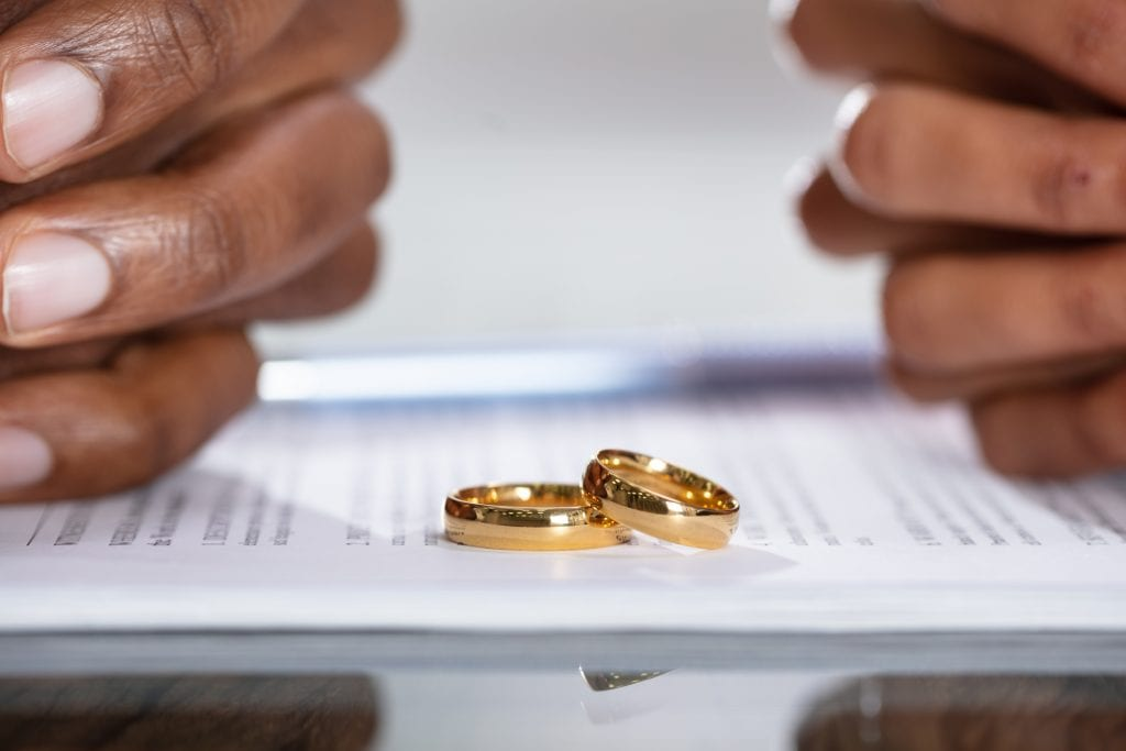 Couple removes wedding bands and signs divorce papers.