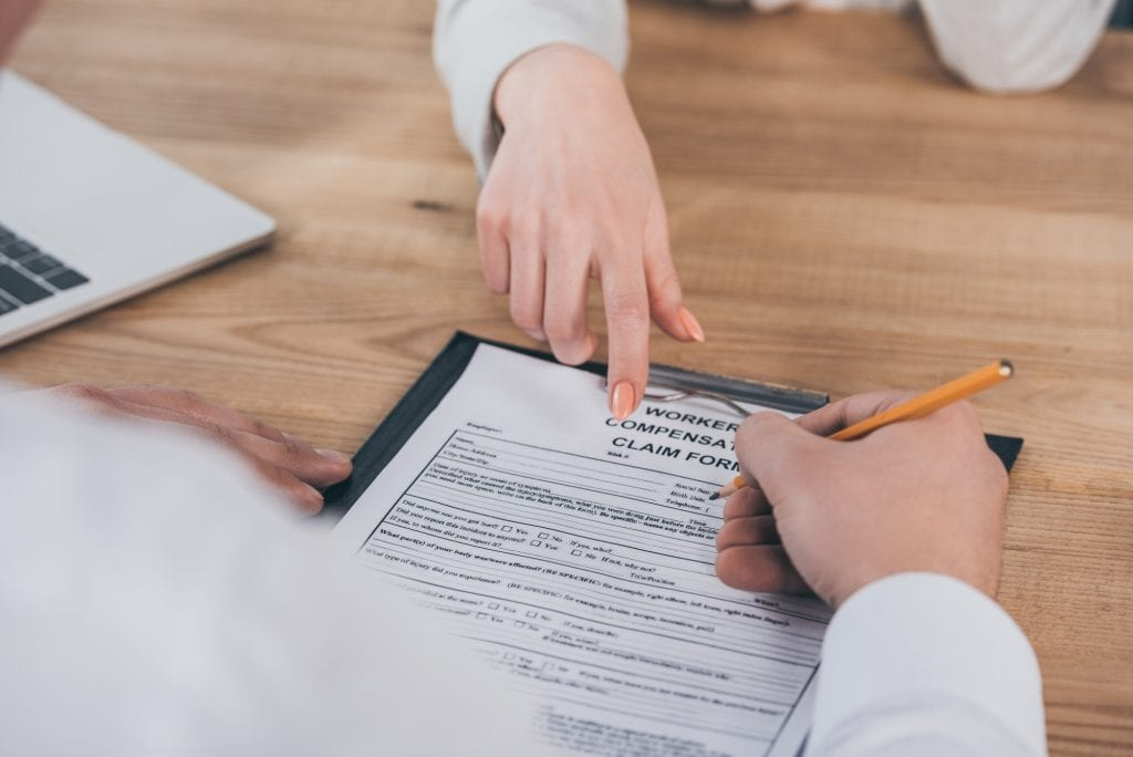 Employee filing out a workers' compensation claim form following an on the job injury.