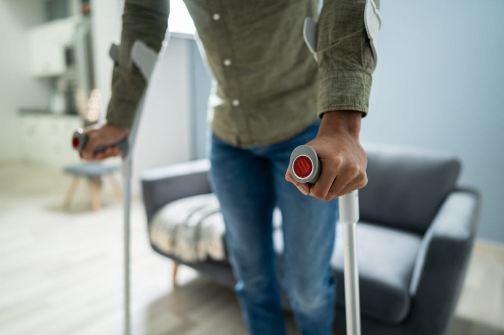 Man learning to walk using crutches following a workplace injury. Workers' compensation can cover lost wages, medical expenses and more.