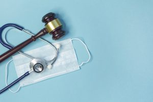 Legal gavel with stethoscope and medical mask, symbolizing personal injury claims during COVID-19.