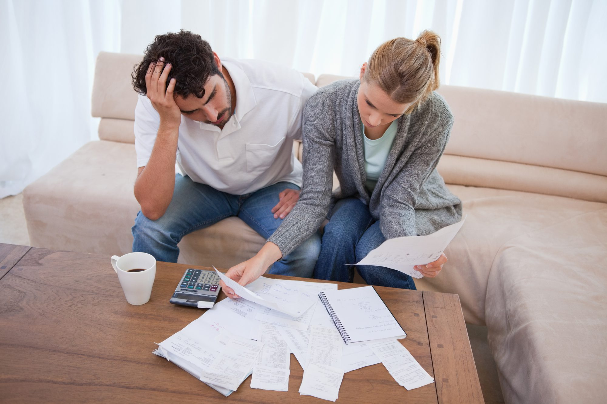 Couple paying bills and contemplating debt consolidation vs. personal bankruptcy.